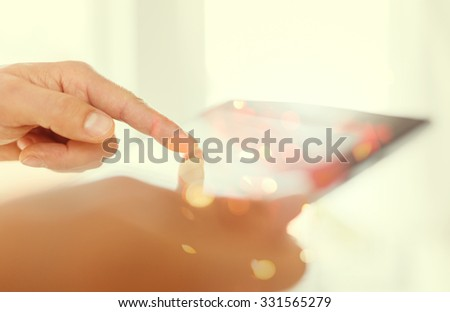 Man hand touching screen on modern tablet pc. Close-up image with shallow depth of field. Tinted photo with some visual effects. - stock photo