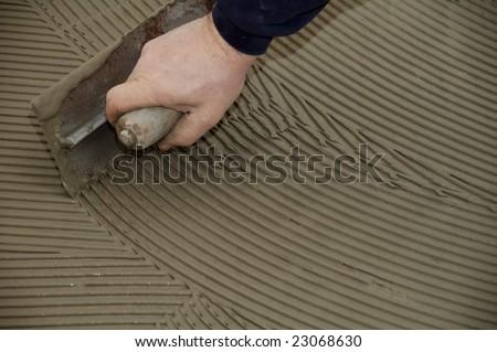 man hand troweling adhesive for ceramic tile flooring - stock photo