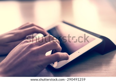 Man hand typing on the tablet screen surface. - vintage style filter - stock photo