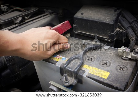 man hand use coins to open the lid for check the battery solution. Thailand Eco Car 1600cc with open hood show parts in side. - stock photo