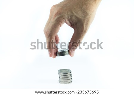 Man hand use finger to put down coin to pile of coins - stock photo