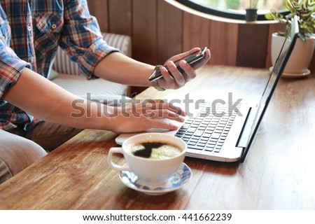 man hand use phone and laptop, Hands multitasking man working on laptop connecting wifi internet, businessman busy at office desk, finger typing on laptop computer sitting at wooden table.coffee shop  - stock photo
