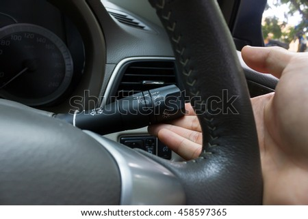 man hand use the signal switch. Car interior detail