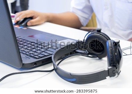 Man hand using keyboard and mouse to control laptop with headphone beside, working in music editing studio production - stock photo