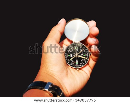 Man hand with a black and silver compass on black close up view. - stock photo