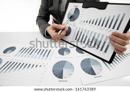man hand with business report on table - stock photo