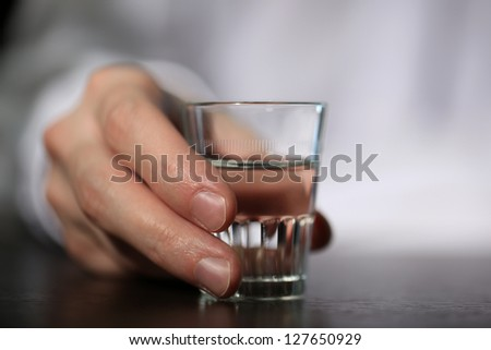 Man hand with glass of vodka , close up - stock photo