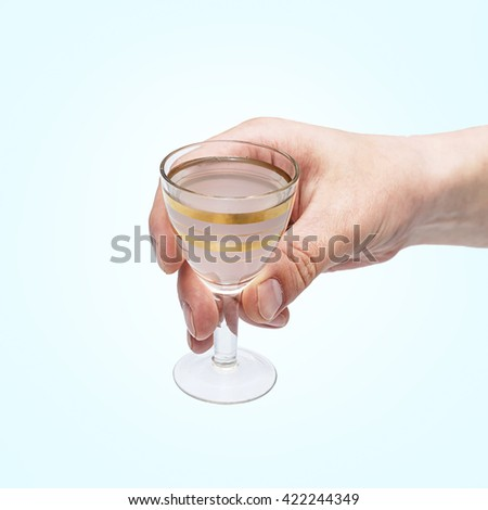 Man hand with glass of vodka , close up, Shot glasses of vodka on blue background, addiction to alcohol.  studio shot - stock photo