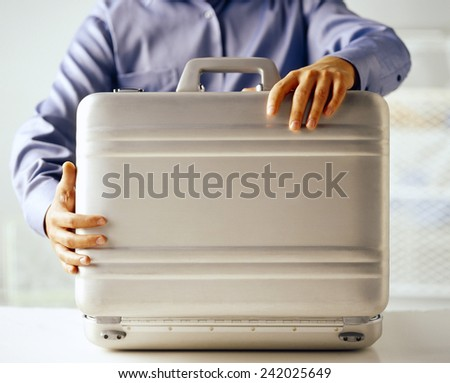 Man hand with metallic security suitcase - stock photo