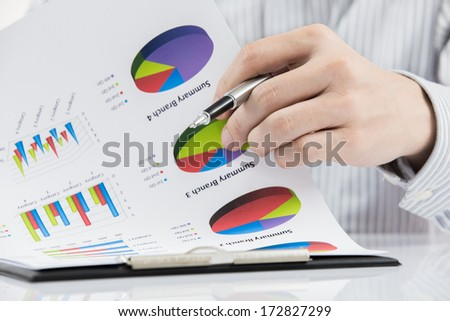 man hand with pen and business report on table - stock photo