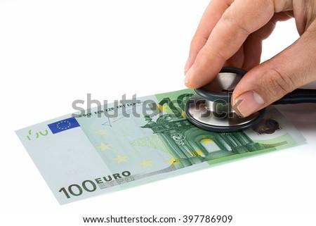 Man hand with phonendoscope auscultating 100 euro banknote - stock photo