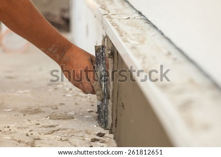 Man hand with trowel plastering a foundation of house - stock photo