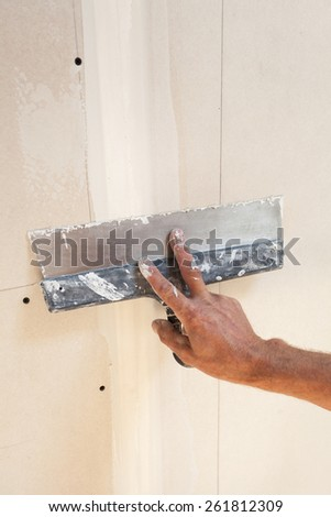 Man hand with trowel plastering a plasterboard - stock photo