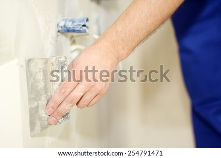 Man hand with trowel plastering a wall, skim coating plaster walls