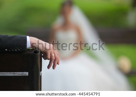 Man hand with wedding ring on blurred bride silhouette background