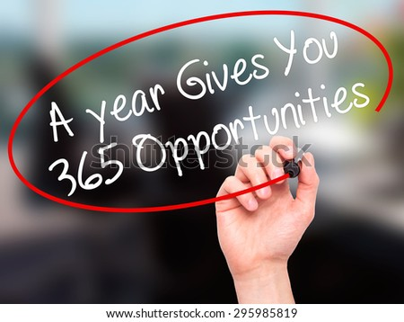 Man Hand writing A year Gives You 365 Opportunities with black marker on visual screen. Isolated on office. Business, technology, internet concept. Stock Photo - stock photo