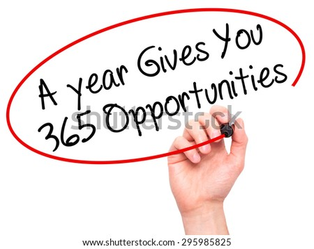 Man Hand writing A year Gives You 365 Opportunities with black marker on visual screen. Isolated on white. Business, technology, internet concept. Stock Photo