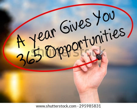 Man Hand writing A year Gives You 365 Opportunities with black marker on visual screen. Isolated on nature. Business, technology, internet concept. Stock Photo - stock photo