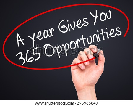 Man Hand writing A year Gives You 365 Opportunities with black marker on visual screen. Isolated on black. Business, technology, internet concept. Stock Photo - stock photo
