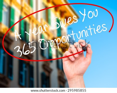 Man Hand writing A year Gives You 365 Opportunities with black marker on visual screen. Isolated on city. Business, technology, internet concept. Stock Photo - stock photo