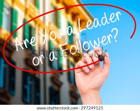 Man Hand writing Are You a Leader or a Follower? with black marker on visual screen. Isolated on city. Business, technology, internet concept. Stock Photo - stock photo