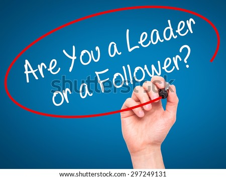 Man Hand writing Are You a Leader or a Follower? with black marker on visual screen. Isolated on blue. Business, technology, internet concept. Stock Photo - stock photo