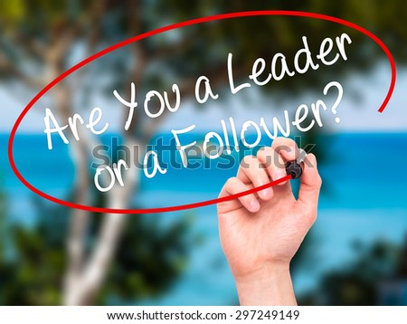 Man Hand writing Are You a Leader or a Follower? with black marker on visual screen. Isolated on nature. Business, technology, internet concept. Stock Photo - stock photo