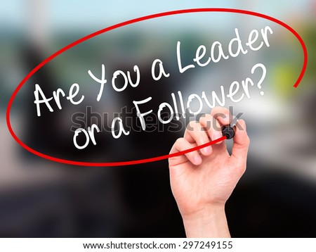 Man Hand writing Are You a Leader or a Follower? with black marker on visual screen. Isolated on office. Business, technology, internet concept. Stock Photo - stock photo