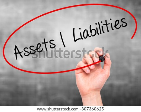 Man Hand writing Assets Liabilities with black marker on visual screen. Isolated on grey. Business, technology, internet concept. Stock Photo - stock photo