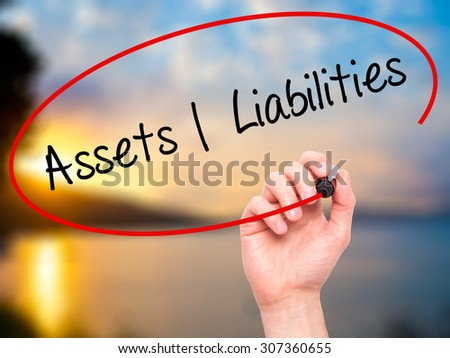 Man Hand writing Assets Liabilities with black marker on visual screen. Isolated on nature. Business, technology, internet concept. Stock Photo - stock photo