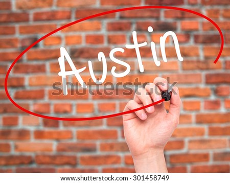 Man Hand writing Austin  with black marker on visual screen. Isolated on bricks. Business, technology, internet concept. Stock Photo - stock photo