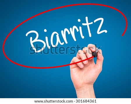 Man Hand writing Biarritz  with black marker on visual screen. Isolated on blue. Business, technology, internet concept. Stock Photo - stock photo