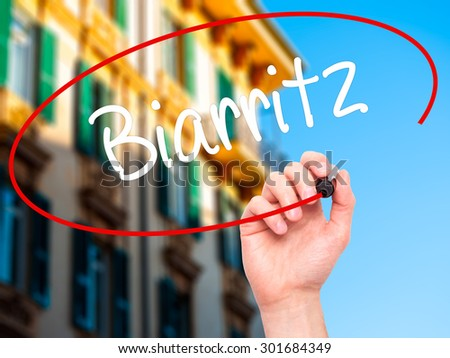 Man Hand writing Biarritz  with black marker on visual screen. Isolated on city. Business, technology, internet concept. Stock Photo - stock photo