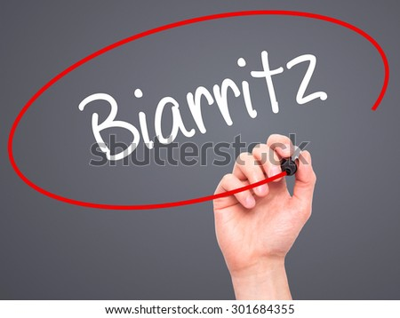 Man Hand writing Biarritz  with black marker on visual screen. Isolated on grey. Business, technology, internet concept. Stock Photo - stock photo