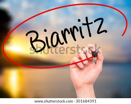 Man Hand writing Biarritz  with black marker on visual screen. Isolated on nature. Business, technology, internet concept. Stock Photo - stock photo