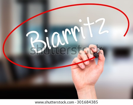 Man Hand writing Biarritz  with black marker on visual screen. Isolated on office. Business, technology, internet concept. Stock Photo - stock photo