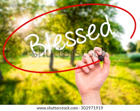 Man Hand writing Blessed  with black marker on visual screen. Isolated on nature. Business, technology, internet concept. Stock Photo - stock photo