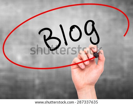 Man Hand writing Blog with marker on transparent wipe board. Isolated on grey. Business, internet, technology concept. Stock Photo - stock photo