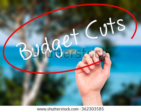 Man Hand writing Budget Cuts with black marker on visual screen. Isolated on background. Business, technology, internet concept. Stock Photo - stock photo