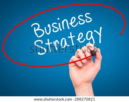 Man Hand writing Business Strategy with black marker on visual screen. Isolated on blue. Business, technology, internet concept. Stock Image - stock photo