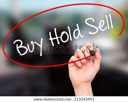Man Hand writing  Buy Hold Sell with black marker on visual screen. Isolated on office. Business, technology, internet concept. Stock Photo - stock photo