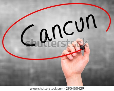Man Hand writing Cancun with black marker on visual screen. Isolated on grey. Travel, technology, internet concept. Stock Image - stock photo
