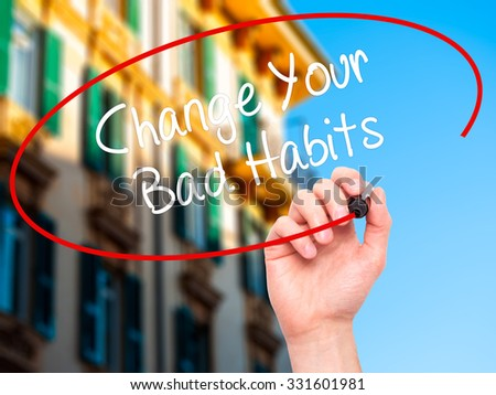 Man Hand writing Change Your Bad Habits  with black marker on visual screen. Isolated on city. Business, technology, internet concept. Stock Photo - stock photo