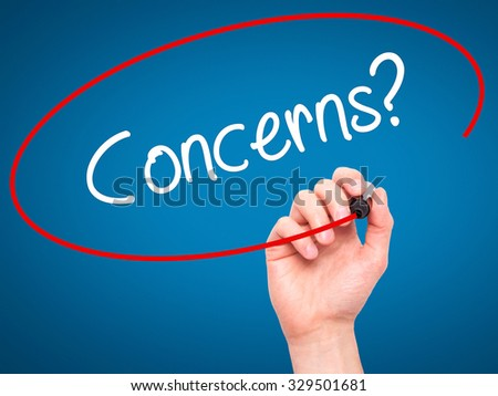 Man Hand writing Concerns? with black marker on visual screen. Isolated on blue. Business, technology, internet concept. Stock Photo - stock photo