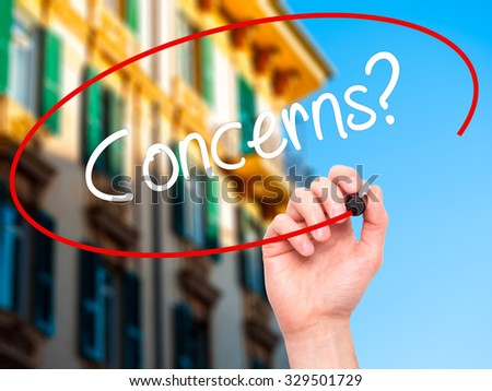 Man Hand writing Concerns? with black marker on visual screen. Isolated on city. Business, technology, internet concept. Stock Photo - stock photo