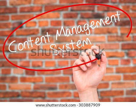 Man Hand writing Content Management System  with black marker on visual screen. Isolated on bricks. Business, technology, internet concept. Stock Photo - stock photo