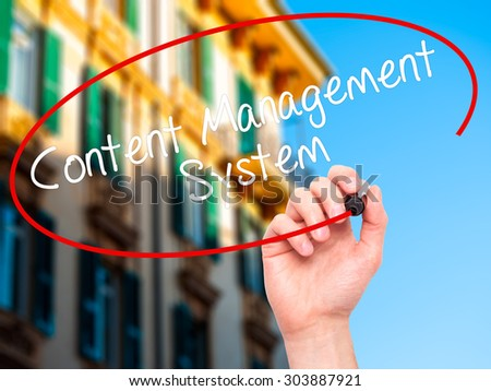 Man Hand writing Content Management System  with black marker on visual screen. Isolated on city. Business, technology, internet concept. Stock Photo - stock photo