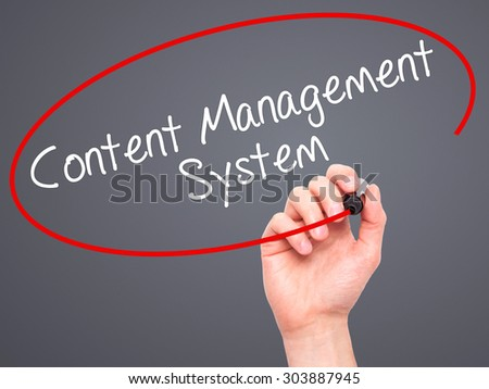 Man Hand writing Content Management System  with black marker on visual screen. Isolated on grey. Business, technology, internet concept. Stock Photo - stock photo