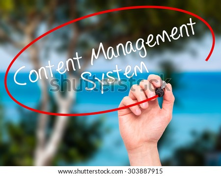 Man Hand writing Content Management System  with black marker on visual screen. Isolated on nature. Business, technology, internet concept. Stock Photo - stock photo