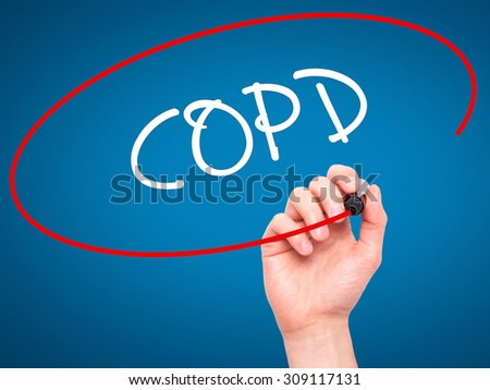 Man Hand writing COPD with black marker on visual screen. Isolated on blue. Business, technology, internet concept. Stock Photo - stock photo